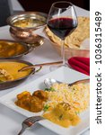 Small photo of Indian curry food spread on a fancy dinner table with rice, laccha paratha, lamb aam wala, saffron malai kofta, red wine.