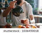 man pours hot tea into glassware | Shutterstock . vector #1036450018