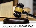judge gavel beside pile of... | Shutterstock . vector #1036473043