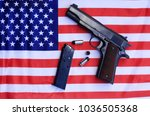 Small photo of 1911 . 45 caliber pistol complete with clip and shells on a American flag. 2nd Amendment Rights to Bear Arms versus Gun Control controversy concepts.