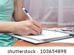 pen in right hand writing on... | Shutterstock . vector #103654898