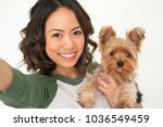 Stock photo closeup portrait of smiling young attractive woman holding yorkshire terrier and taking selfie 1036549459