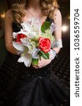 Small photo of Rose and lily bouquet held by unrecognizable teenage girl wearing shimmering black prom gown
