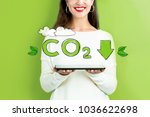 reduce co2 with woman holding a ... | Shutterstock . vector #1036622698
