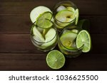 Small photo of Alcoholic drink made with vodka and whiskey, with slices of green apple and lime and ice cubes. Soft focused/shallow depth of field , top angle view of homemade alcoholic drink.