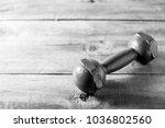 dumbbell on wooden table... | Shutterstock . vector #1036802560