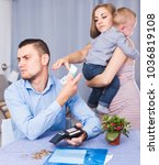 Small photo of Angry female with child extorting money from male with hate indoors