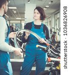 Small photo of Portrait of young repairman and repairwoman standing in bicycle shop