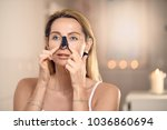 Small photo of Attractive middle-aged blond woman applying an anti-aging face mask to her nose in a bathroom with burning candles in a concept of beauty, skincare and the ageing process with copy space
