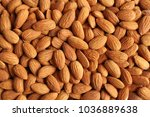 Small photo of Background of big raw peeled almonds situated arbitrarily