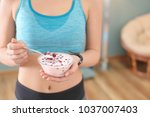 sporty young woman eating... | Shutterstock . vector #1037007403