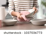 woman wiping dishware with... | Shutterstock . vector #1037036773