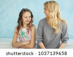 Small photo of Mother and daughter sit next to each other and writhe faces.