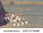 Small photo of Opened Male Leather Wallet With British Different Coins Scattered On The Vintage Wooden Table Background With Copy Space. Financial Concept. Top View .