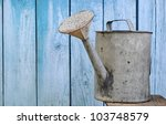 Old Watering Can On Wooden...