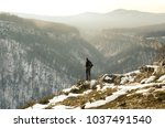 a man stands on the edge of a... | Shutterstock . vector #1037491540