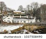 snow falling the old bridge... | Shutterstock . vector #1037508490