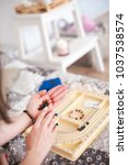 Small photo of Female hands collect a bracelet from natural stones. A woman or girl and a board for collecting bracelets, necklaces. Handmade, hobby, pacification, close-up
