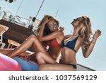 poolside fun. two beautiful... | Shutterstock . vector #1037569129