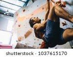 man bouldering at an indoor... | Shutterstock . vector #1037615170