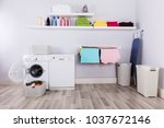 Stock photo basket full of dirty clothes in front of washing machine at laundry room 1037672146