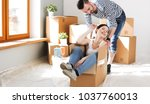 happy young couple unpacking or ... | Shutterstock . vector #1037760013