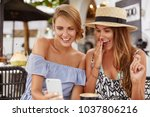 Small photo of Excited beautiful two women watch funny video on modern cell phone, have surprised and happy expressions, spend free tine at outdoor cafeteria, connected to high speed internet. Lifestyle conncept