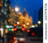 Small photo of Emotional melancholic abstract background with defocused lights bokeh in London, UK behind rain drops in window glass, Focus on few drops due to the shallow depth of field
