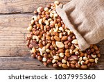 mixed nuts on a wooden table ... | Shutterstock . vector #1037995360