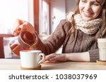 Woman Pours Tea From A Teapot...