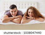 Small photo of Horizontal shot of pleased satisfied family couple lie on comfortable bed, being in good mood after unforgettable night. Lovely curly woman lies close to her boyfriend. Relationship concept.