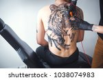 Small photo of A tattoo artist makes a tattoo in the salon on the back of a client. Tattoo of a tiger. The tattoo on his back. Art concept. Close up
