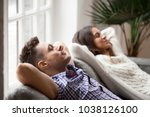 Small photo of Young couple resting on comfortable couch together at home, happy man and woman enjoying relaxation or nap dozing on sofa with eyes closed, calm family breathing fresh air feeling totally relaxed