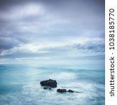 dark rocks in a blue ocean... | Shutterstock . vector #1038185770