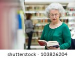 Portrait of old retired woman choosing book in library and taking it from shelf - stock photo