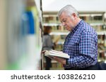 Portrait of senior retired man choosing book in library from shelf. Copy space - stock photo