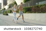 Small photo of LENS FLARE: Active girl and boy on a delightful jog in sunny spring in big city. Fit couple enjoy spending time together jogging through sunlit city streets in summer. Young athletic people running