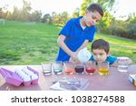 brothers coloring easter eggs | Shutterstock . vector #1038274588