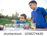 brothers coloring easter eggs | Shutterstock . vector #1038274630