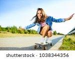 smiling woman riding longboard...   Shutterstock . vector #1038344356