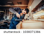 man builds furniture in the... | Shutterstock . vector #1038371386