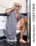 a cheerful man in the bathrobe... | Shutterstock . vector #1038375808