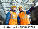 Small photo of Low angle view of highly professional engineers wearing uniform and protective helmets standing at spacious production department of modern plant and discussing results of accomplished work.