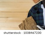Casual outfit and accessories, Top view of flannel plaid shirt , chino pants and casvas sneakers on wooden backgroud with copy space