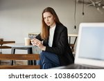 Small photo of Woman is insulter with offensive words of stranger sitting with laptop. Portrait of annoyed attractive woman in cafe, holding smartphone and drinking coffee, frowning at person who tells rude things