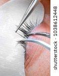 Small photo of Eyelash extension procedure, woman eye with Long eyelashes