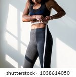 asian woman measuring waist size | Shutterstock . vector #1038614050