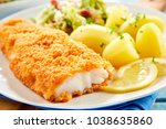 Small photo of Close up view of crispy breaded fish served on plate with potatoes