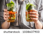 A Woman Holds And Eats Salad I...