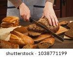 woman cutting bread on wooden... | Shutterstock . vector #1038771199